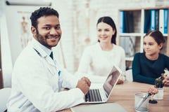 Indischer Doktor, der Patienten im Büro sieht Doktor spricht, um zu bemuttern und die Tochter, die Laptop verwendet lizenzfreies stockfoto