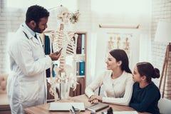 Indischer Doktor, der Patienten im Büro sieht Doktor zeigt Skelett, um zu bemuttern und Tochter lizenzfreie stockfotografie
