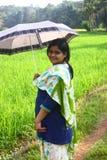 Indischer Dorf-Mädchen-Holding-Regenschirm im Sonnenlicht Stockfoto