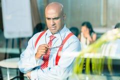 Indischer Geschäftsmann, der am Bürofenster denkt Lizenzfreie Stockbilder