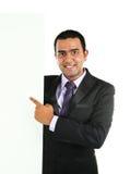 Indischer Geschäftsmann, der weißes Plakat anzeigt Stockfotografie