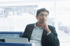 Indischer Geschäftsmann, der einen Gedanken am Flughafen hat Stockfotografie