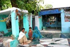 Indischer glücklicher junger Mann mit seiner Familie, die Tee oder Kaffee, außerhalb dort des Hauses trinkt Stockfoto