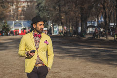 Indischer gutaussehender Mann, der in einem städtischen Zusammenhang simst Stockfotos
