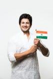 Indischer hübscher Junge oder Mann in der weißen ethnischen Abnutzung, die indische Staatsflagge hält und den Patriotismus, stehe Stockfotos