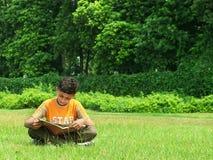 Indischer Junge, der draußen studiert stockfotografie