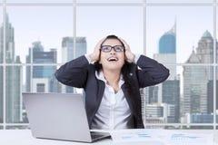 Indischer junger Angestellter schreit im Büro Stockfotografie