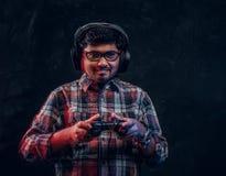 Indischer Kerl in den drahtlosen Kopfhörern, die Steuerknüppel- und Spielvideospiele auf der Konsole steht im Studio halten stockbild