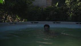 Indischer Kerl in schwimmenden Hemden tragen Taucherbrille und Schwimmen im Pool der Kinder stock video footage