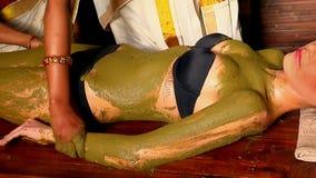 Indischer Kosmetiker der Frauen wendete therapeutischen Lehm von natürlichem am Körper des Patienten an stock footage