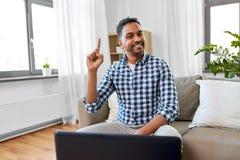Indischer männlicher Blogger, der oben Finger zu Hause zeigt lizenzfreie stockbilder