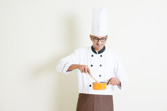 Indischer männlicher Chef in der Uniform, die Lebensmittel zubereitet Stockfoto