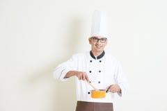 Indischer männlicher Chef in der Uniform Lebensmittel kochend Lizenzfreies Stockfoto