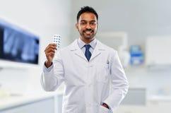 Indischer männlicher Zahnarzt mit Pillen an der zahnmedizinischen Klinik stockbild