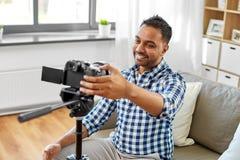 Indischer m?nnlicher Videoblogger, der zu Hause Kamera justiert stockfoto