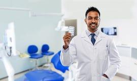 Indischer m?nnlicher Zahnarzt mit Pillen an der zahnmedizinischen Klinik stockbilder
