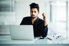 Indischer Mann Concetrated, der im Büro lächelt und arbeitet lizenzfreie stockfotografie