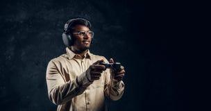Indischer Mann in den drahtlosen Kopfhörern, die Steuerknüppel- und Spielvideospiele auf der Konsole halten Abschluss oben stockfotos