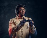 Indischer Mann in den drahtlosen Kopfhörern, die Steuerknüppel- und Spielvideospiele auf der Konsole halten Abschluss oben lizenzfreies stockfoto