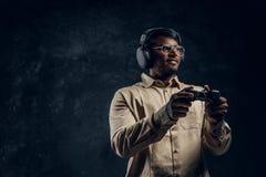 Indischer Mann in den drahtlosen Kopfhörern, die Steuerknüppel- und Spielvideospiele auf der Konsole halten Abschluss oben stockbilder
