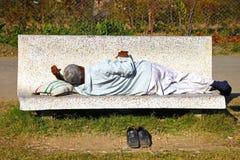Indischer Mann, der auf einer Bank schläft Lizenzfreies Stockbild