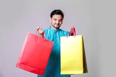 Indischer Mann in der ethnischen Abnutzung mit den Einkaufstaschen, lokalisiert über weißem Hintergrund lizenzfreies stockbild
