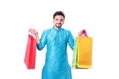 Indischer Mann in der ethnischen Abnutzung mit den Einkaufstaschen, lokalisiert über weißem Hintergrund stockfotos