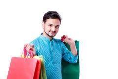 Indischer Mann in der ethnischen Abnutzung mit Einkaufstaschen und dem Zeigen des mobilen Schirmes, lokalisiert über weißem Hinte stockfotografie