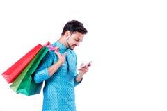 Indischer Mann in der ethnischen Abnutzung mit Einkaufstaschen und dem Zeigen des mobilen Schirmes, lokalisiert über weißem Hinte lizenzfreie stockbilder