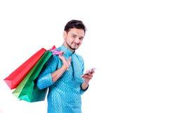 Indischer Mann in der ethnischen Abnutzung mit Einkaufstaschen und dem Zeigen des mobilen Schirmes, lokalisiert über weißem Hinte stockfoto