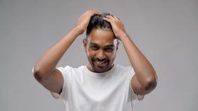Indischer Mann, der Haarwachs aufträgt oder Gel anredet stock footage