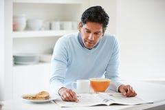 Indischer Mann, der zu Hause Frühstück genießt Stockfotos
