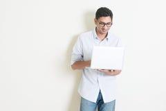 Indischer Mann des zufälligen Geschäfts, der Laptop verwendet Stockfotografie