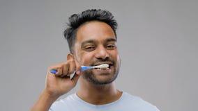 Indischer Mann mit den Zahnbürstenreinigungszähnen stock video