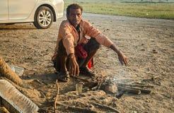 Indischer obdachloser Mann sitzt neben einem Feuer, um warm zu halten auf einem kalten Wintermorgen Stockfoto