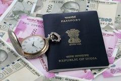 Indischer Pass, neue Rupien-Währung und antike Uhr Lizenzfreie Stockbilder