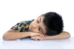 Indischer Schuljunge, der auf Schreibtisch schläft Stockbild