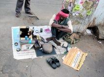 Indischer Schuster, der an Straße arbeitet Stockbilder