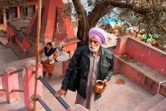 Indischer Senior im Turban steigt oben die Schritte auf hindischem Tempel Stockbild
