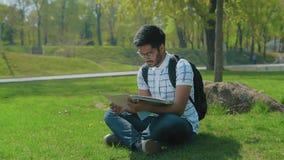 Indischer Student in den Gläsern mit einem Rucksack das Material vom abstrakten Sitzen auf dem Rasen im Stadt-Park studierend stock footage