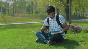 Indischer Student in den Gläsern mit einem Rucksack, der durch das abstrakte Sitzen auf dem Rasen im Stadt-Park schaut stock video footage
