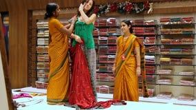 Indischer Verkäufer Puts auf rotem Sari zur Frau stock footage