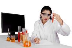 Indischer weiblicher Wissenschaftler mit Reagenzglas auf Studio Lizenzfreie Stockfotografie
