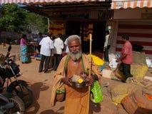 Indisches hindisches sadhu bitten auf der Straße, die einen kleinen Affen in der Stahlschüssel trägt Stockfotografie