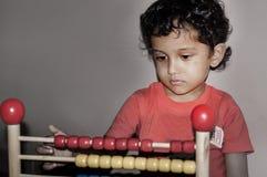 Indisches Kind, das Abakus spielt Stockfoto