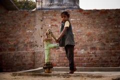 Indisches kleines Mädchen auf Handpumpe Lizenzfreies Stockbild