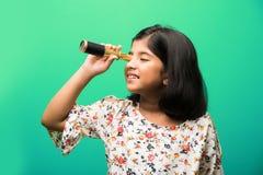 Indisches kleines Mädchen, das Teleskop verwendet und Weltraumforschung studiert stockfoto