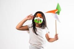 Indisches kleines Mädchen und tricolour das Gesicht, die Windmühle hält, bildeten vom Safran, grünes und weißes Farbpapier, glück Stockbild
