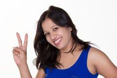 Indisches Mädchen, das ein blaues ärmelloses T-Shirt zeigt Sieg Sig trägt Stockfoto