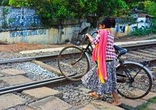 Indisches Mädchen mit einem Fahrrad führt Eisenbahnen Stockbilder